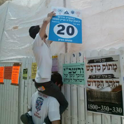 Hanging signs in Meron to allow the crowd to more easily identify there whereabouts to first responders
