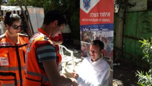 Eliana and Avner in their EMT vests during a health fair at the home of the British Ambassador to Israel