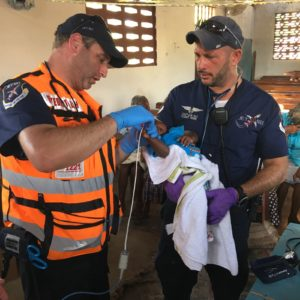 CEO of JET911 Eli Rowe (right) together with Dovi Maisel (left) treating a child in Haiti