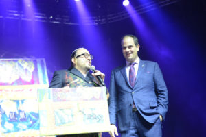 Eli Beer receives the painting from Lipa Schmeltzer on stage at the Annual United Hatzalah United for Life Concert (Credit: Oren Lumenkrantz)