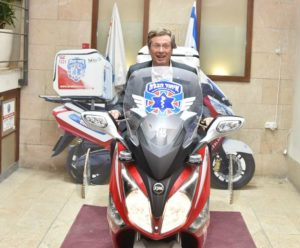 Toronto Mayor John Tory sits astride an ambucycle, the signature vehicle of the organization during his visit to United Hatzalah headquarters.