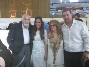 Sara Lee and Yoni take a picture with their Sarah's grandfather during the wedding.