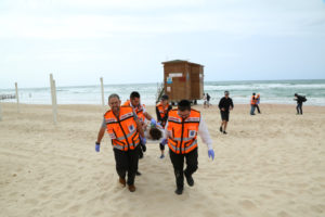 Rescue on a beach involving numerous responders and an ATV.