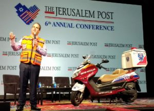 Eli Beer on stage with a United Hatzalah ambucycle. (Photo Credit: Joel Leyden - Twitter)