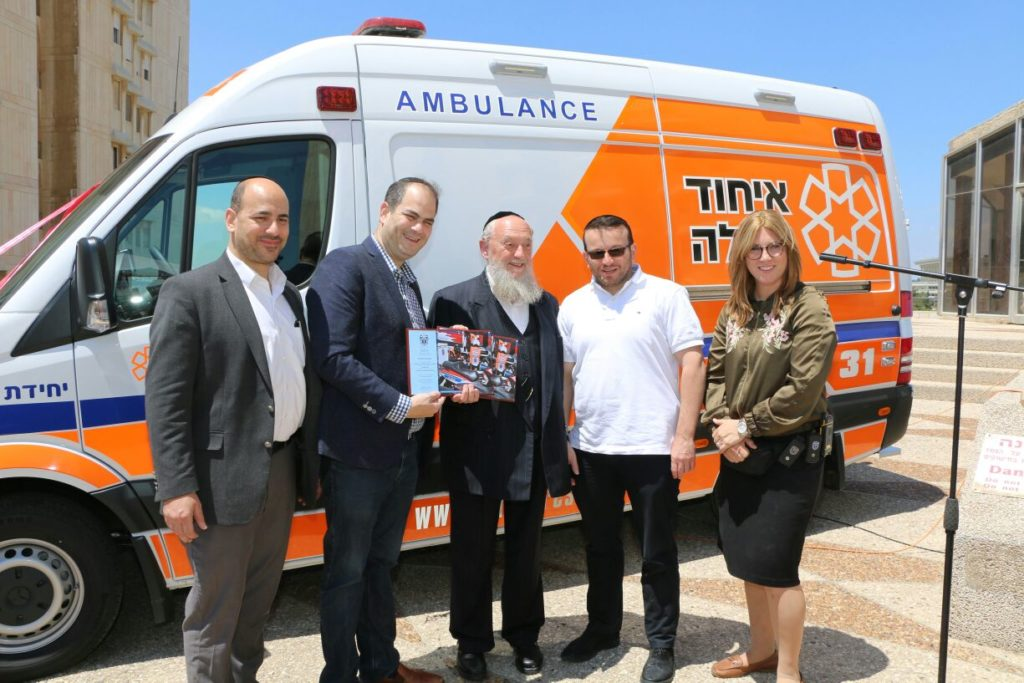 ELi Pollack, Eli Beer, Rabbi  Israel Braun, Moshe Teitelbaum, and Miriam Ballin stand in front of the new ambulance