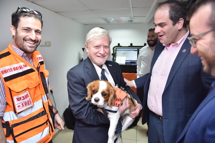 Shapria (Center) holding Psychotrauma and Crisis Response Unit K-9 Responder Lucy. Also photographed EMT Moshe Jaffe (Left), United Hatzalah Security Liasion Shmulik Avraham, Founder Eli Beer, and CEO Moshe Teitelbaum (far right)