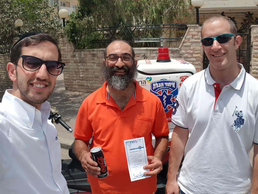 Ariel Ben David and Avi Marcus treat volunteers to a cold beverage while giving them a letter of thanks in the field.