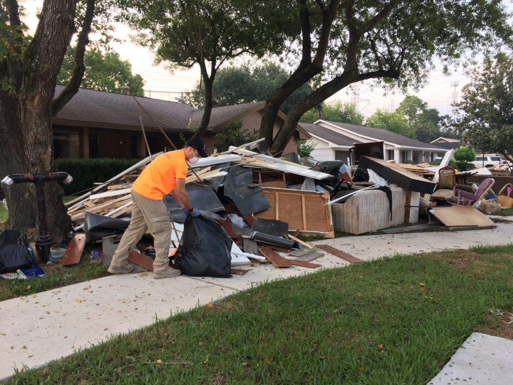 IRC team member Josh Cerf helps people clean their house from debris in Houston