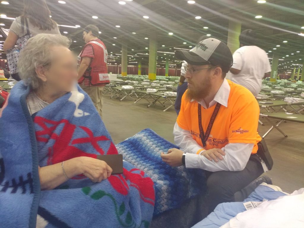 Avi Tennenbaum speaking with an evacuee in Dallas